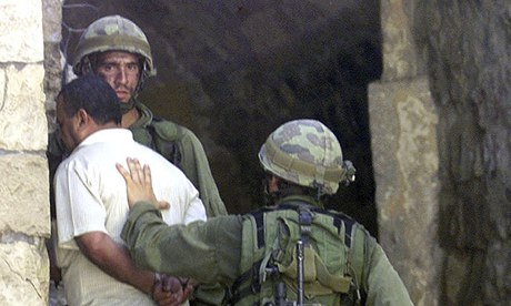 Israeli soldiers arrest a Palestinian in the West Bank town of Nablus