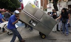 A man moves a fridge he bought in Caracas after President Maduro took over shops to ease shortages
