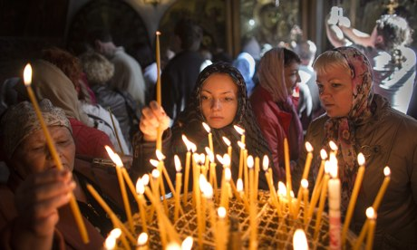 Pilgrims light candles in the Church of the Nativity, in the West Bank town of Bethlehem