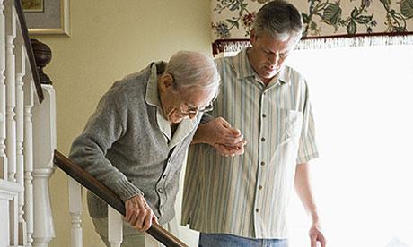 Carer helps elderly man walk downstairs