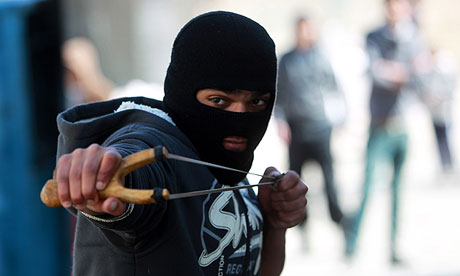 a Palestinian youth uses a catapult against riot police during riots in Hebron's Arroub refugee camp