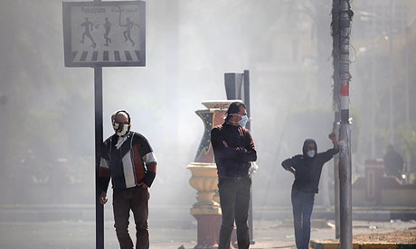 Egyptian protesters cover their faces as police fire tear gas in Port Said. Six people have died