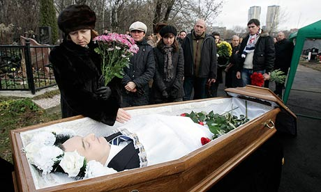 Widow Zharikova grieves over her husband Magnitsky's body during his funeral at a cemetery in Moscow