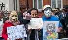 Assange supporters in David Cameron and Anonymous masks wait for the WikiLeaks founder