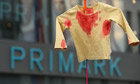 A Blockupy campaigner Holds Up a blood-stained shirt at a protest at a Primark store in Frankfurt