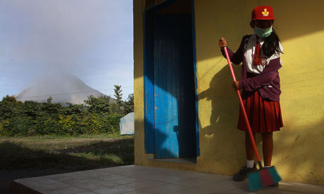 An Indonesian girl sweeps volcanic ash from outside a classroom as Mount Sinabung spews steam and ash behind her. Photograph: Kharisma Tarigan/AFP/Getty