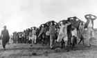 Mau Mau suspects being led away by police in Kenya's Rift Valley in 1952.