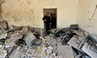 Policemen look at the damage caused after a bomb explosion at a police station in Benghazi
