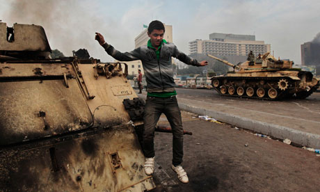 An Egyptian anti-government protester jumps from a burned armored personnel carrier