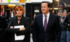 David Cameron walks through a street market with retail expert Mary Portas