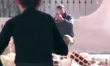 Syrian military soldier aims gun at young boy