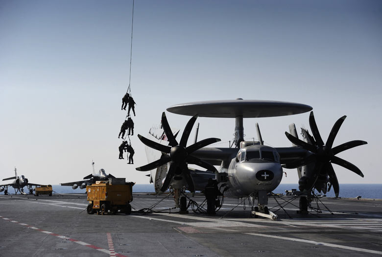 French soldiers are winched down from a Caracal helicopter next to a French E2C-Hawkeye plane