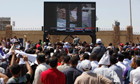 Egypt's ousted President Hosni Mubarak  is seen on a TV screen as he enters the courtroom