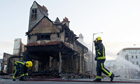 Firemen douse the charred remains of the Reeves furniture store in Croydon