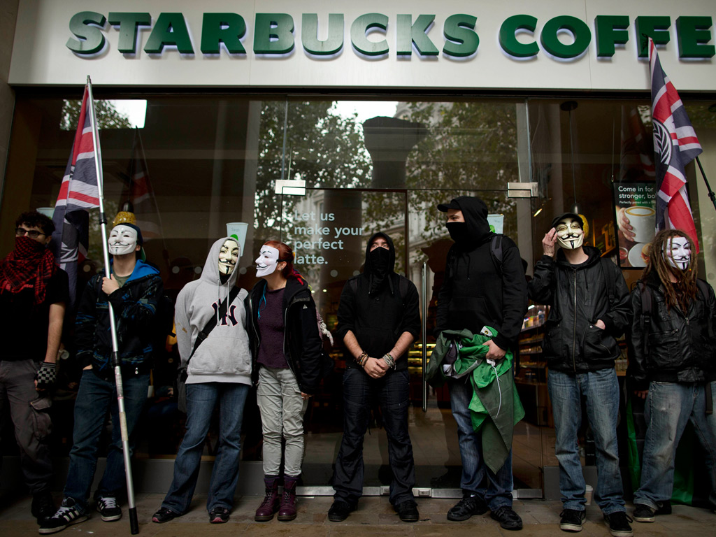 Demonstrators stand outside a branch of Starbucks as they gather near St Paul's Cathedral