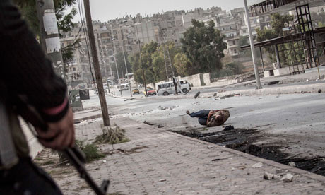 A Syrian civilian falls down on the street after being shot in his stomac
