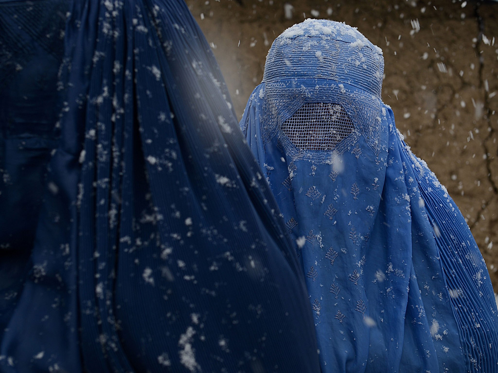 Internally displaced Afghan women from Helmand province wait to receive winter supplies