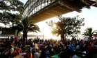 People wait under Sydney Harbour Bridge in anticipation of New Year's Eve fireworks