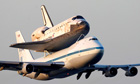 Space shuttle Discovery attached to a jet plane