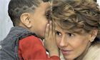 young boy whispering to asma al-assad