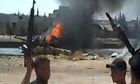 Free Syrian Army members in front of burning tank
