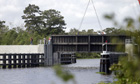 A crane lowers a flood gate into the Hero canal in Belle Chasse, Louisiana