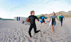 Surfers running down the beach in Croyde, Devon