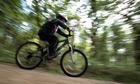 Boy cycling on a path through woodland