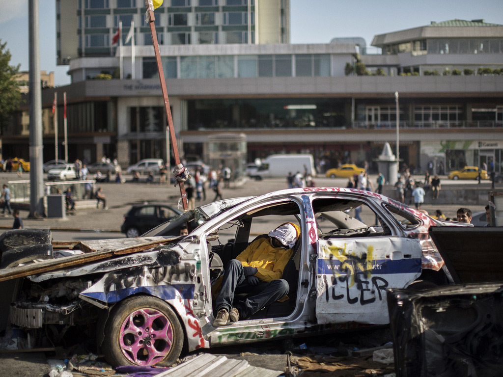A man sleeps in the wreckage of a car outside Gezi park in Istanbul