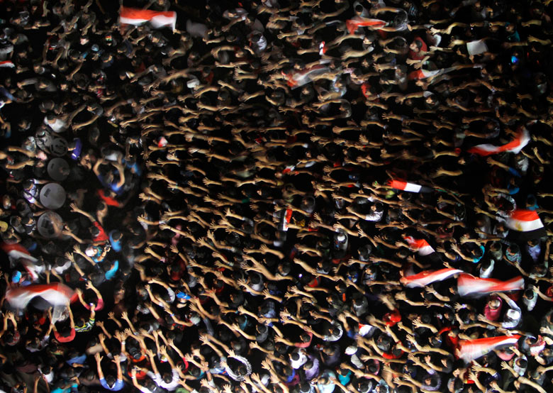 Egyptian protesters wave their hands and hold national flags during a demonstration against president Mohamed Morsi in Tahrir Square Amr Nabil/AP