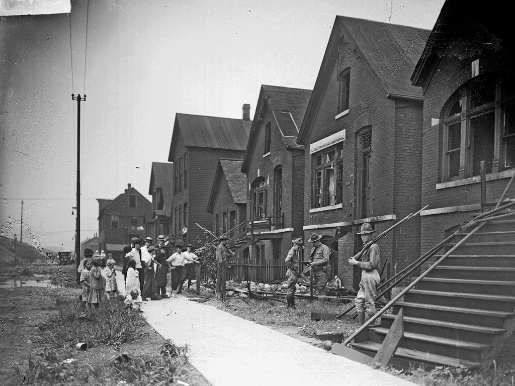 Soldiers with rifles stand guard at vandalized houses, Chicago, Illinois, July, 1919