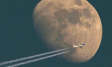 A jet it's vapour trail streaming out behind flies past the waxing moon over the city of Aarau