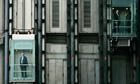 People are seen riding elevators on a building in central London's City financial district