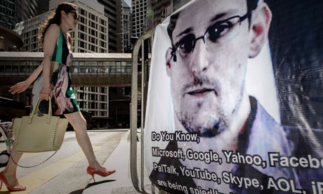 Woman walks past Edward Snowden banner in Hong Kong