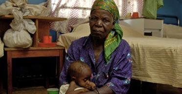 Llania Banda holds her ailing granddaughter