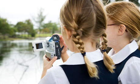 Two schoolgirls using a video camera