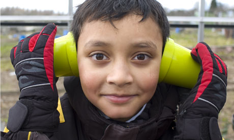 A child holds plant pots to his ears