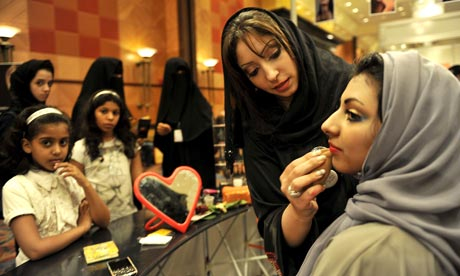 A Saudi woman applies makeup