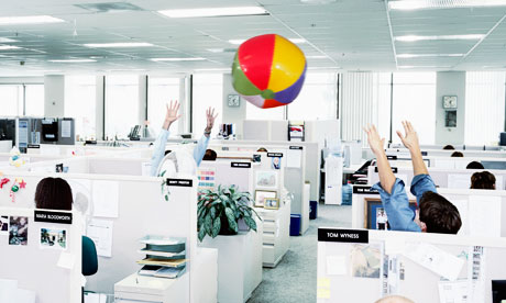 People throwing a beach ball around an office