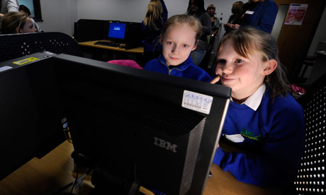 Two young schoolgirls looking at a computer screen