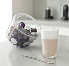 Nespresso pods in a glass bowl placed next to a cup of coffee in a kitchen