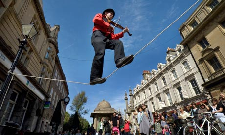 A Street Theatre busker plays a violin while balancing  on a tightrope during Brighton Festival