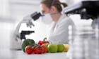 Scientist in lab with fruit and vegetables in foreground