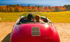 Brand USA: USA, Vermont, Lamoille County, Stowe, Couple sitting in a vintage sports car