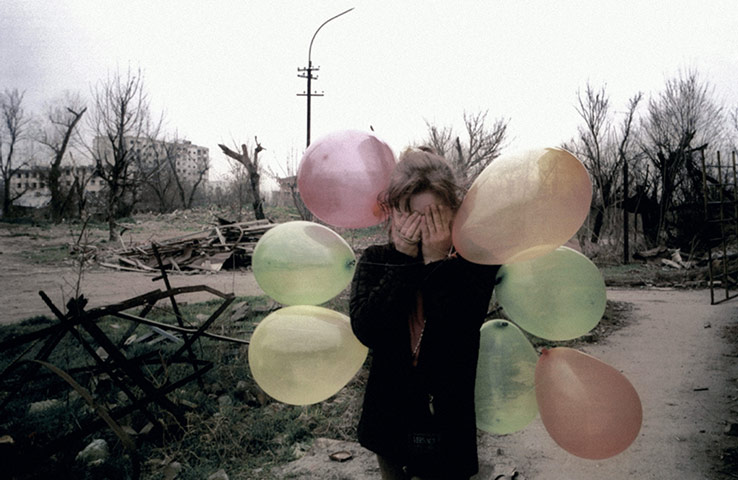 Europe 1945-2011: A girl festooned with balloons covers her eyes amid the ruins of Grozny
