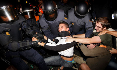 Riot police struggle with protesters during demonstrations in Madrid