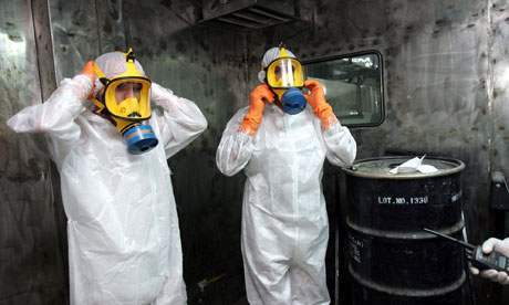 Two technicians in protective wear, alongside a box containig uranium ore concentrate, in Iran