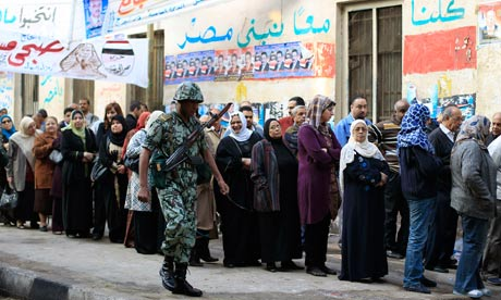 An Egyptian soldier guards as Egyptians queue to cast their votes in Cairo