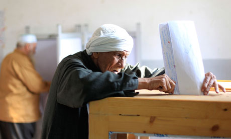 An old man casts his vote at a polling station during parliamentary elections in Cairo, Egypt