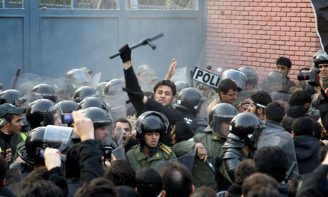 Iranian riot police stand guard as protesters gather outside the British embassy in Tehran